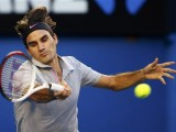 Roger Federer of Switzerland hits a return to Bernard Tomic of Australia during their men's singles match at the Australian Open tennis tournament in Melbourne